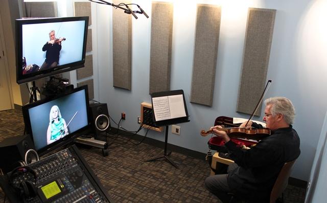 Pinchas Zukerman au studio Hexagone, donnant une leçon de violon à une élève de l'Académie Sibelius, en Finlande (écran télé du bas)