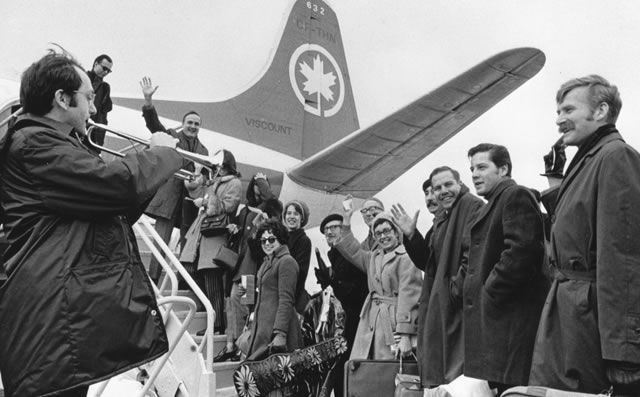 Members of the NAC Orchestra embark on a tour in 1972 to the sounds of Frederick Mills�s trumpet. Founding Orchestra conductor Mario Bernardi waves from the top of the stairs. | © NAC Archives